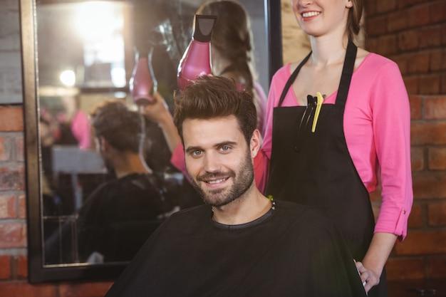 Fryzjer stylizuje włosy klientów