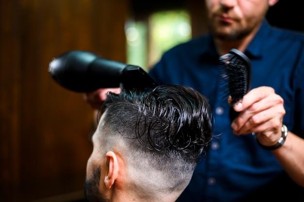 Fryzjer suszący włosy swojego klienta