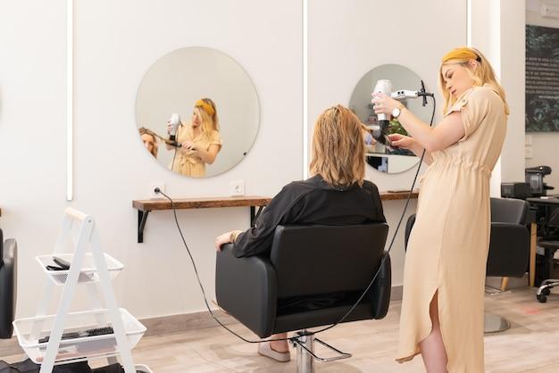 Fryzjer suszenie włosów blond kobieta w jej salonie fryzjerskim. widok z tyłu