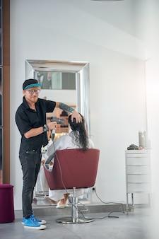 Fryzjer suszy modelkom mokre włosy i patrzy w kamerę