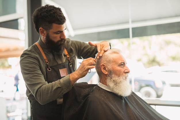 Fryzjer tnący klient w fryzjera sklepie