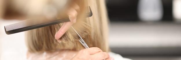 Fryzjer trzyma w dłoniach grzebień i nożyczki i tnie włosy klientów