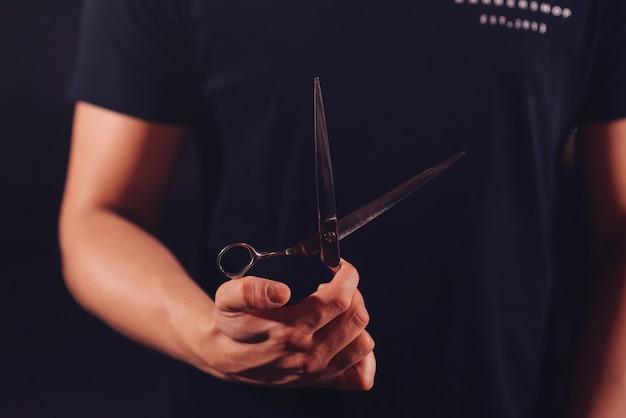 Fryzjer trzyma w dłoniach nożyczki