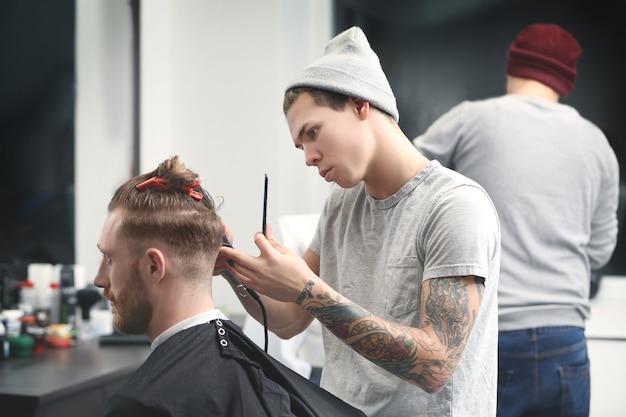 Fryzjer tworzący nowoczesną męską fryzurę