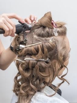 Fryzjer tworzy wizerunek panny młodej blondynki. ścieśniać.