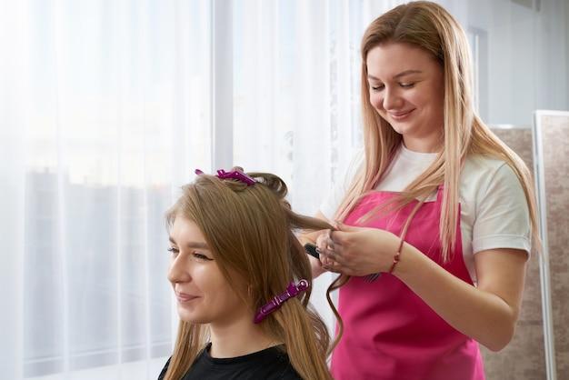 Fryzjer układa włosy klienta w gabinecie kosmetycznym