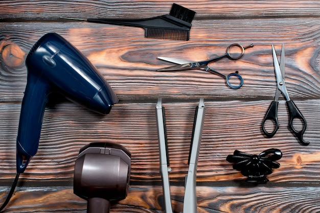 Fryzjer ustawiający z różnorodnymi akcesoriami na drewnianym tle
