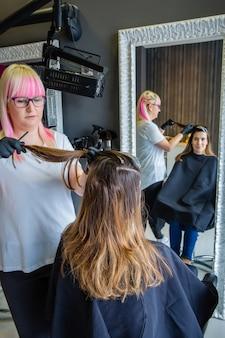 Fryzjer w czarnych rękawiczkach czesze włosy pięknej młodej kobiety w trakcie zmiany koloru włosów