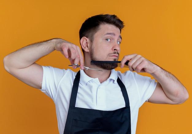 Fryzjer w fartuchu czesanie i strzyżenie brody, stojący nad pomarańczową ścianą