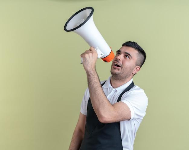 Fryzjer w fartuchu krzyczy do megafonu z agresywnym wyrazem twarzy stojąc na zielonym tle