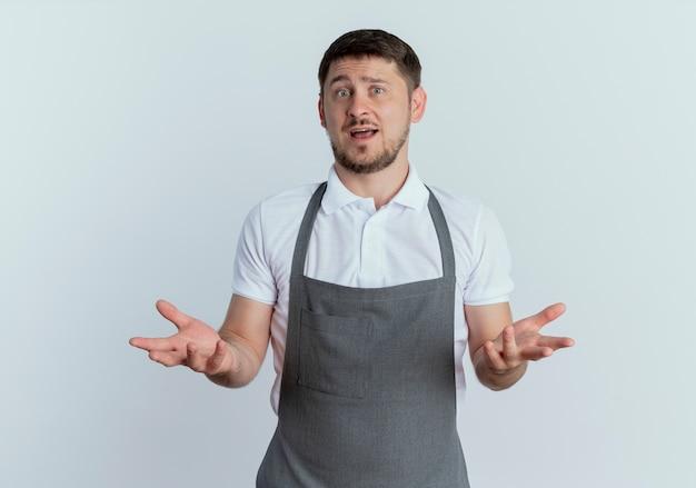 Fryzjer w fartuchu patrząc na kamerę zdezorientowany z wyciągniętymi rękami, pytając o coś lub kłócąc się, stojąc na białym tle