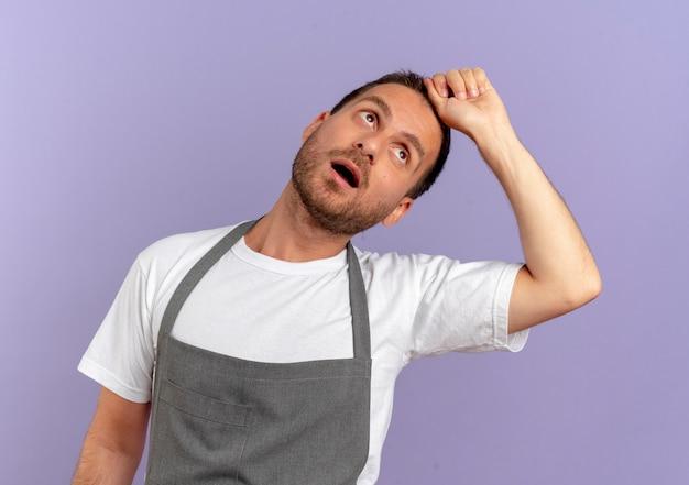 Fryzjer w fartuchu patrząc w górę zaniepokojony i zmęczony stojący nad fioletową ścianą