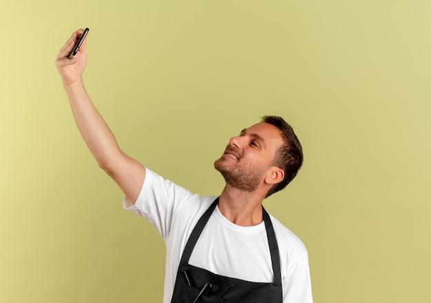 Fryzjer w fartuchu przy selfie przy użyciu smartfona, uśmiechając się wesoło, stojąc nad jasną ścianą