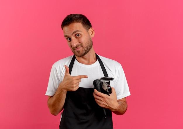 Fryzjer w fartuchu trzyma szczotkę do włosów i trymer, wskazując palcem na to, uśmiechnięty pewnie stojąc nad różową ścianą