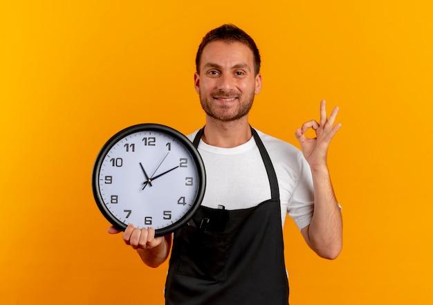 Fryzjer w fartuchu trzyma zegar ścienny patrząc do przodu, uśmiechając się wesoło, pokazując znak ok stojącego nad pomarańczową ścianą