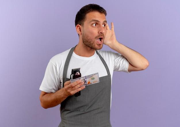 Fryzjer w fartuchu, trzymając maszynę do cięcia włosów i gotówkę, trzymając rękę przy uchu, próbując słuchać stojąc nad fioletową ścianą