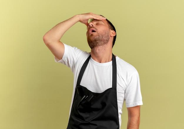 Fryzjer w fartuchu, trzymając rękę nad głową, wyglądający na zmęczonego i znudzonego stojącego nad jasną ścianą