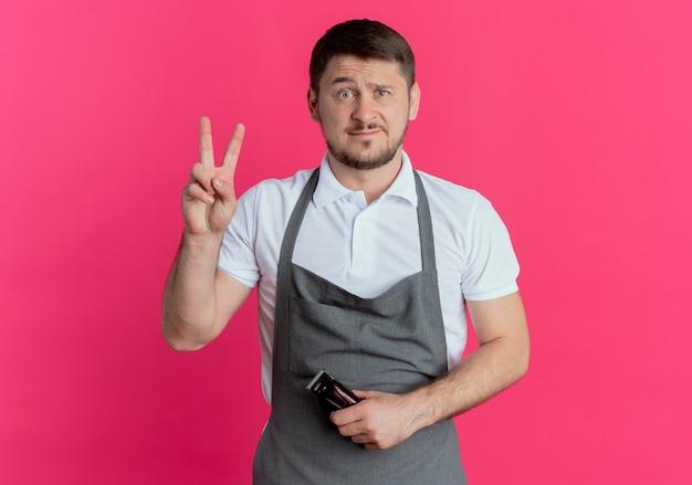 Fryzjer w fartuchu trzymając trymer do brody patrząc na kamery, pokazując niezadowolony numer dwa stojąc na różowym tle