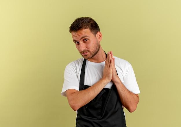 Fryzjer w fartuchu trzymający dłonie razem, patrząc do przodu z poważną twarzą, czekający na coś stojącego nad jasną ścianą