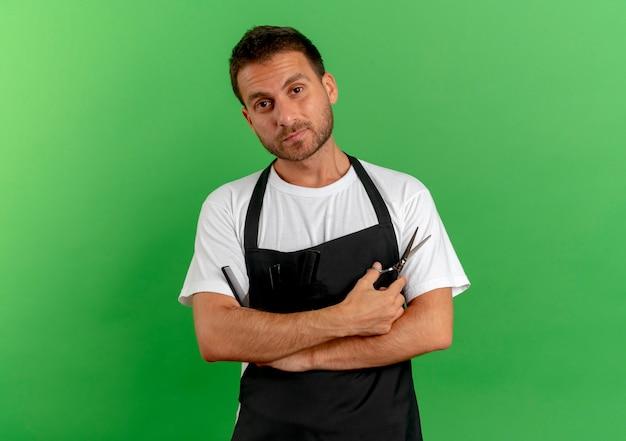 Fryzjer w fartuchu trzymający grzebień i nożyczki, patrząc do przodu z pewnym siebie wyrazem, stojący nad zieloną ścianą 2