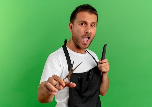 Fryzjer w fartuchu trzymający grzebień i nożyczki, patrzący do przodu z pewnym siebie wyrazem, stojący nad zieloną ścianą 4