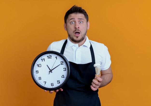 Fryzjer w fartuchu trzymający zegar ścienny i pędzel do golenia zdumiony i zaskoczony stojąc nad pomarańczową ścianą