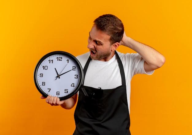 Fryzjer w fartuchu trzymający zegar ścienny, patrząc na niego zdezorientowany i bardzo zaniepokojony, stojący nad pomarańczową ścianą