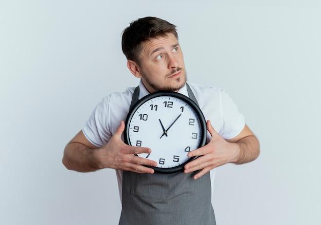 Fryzjer w fartuchu trzymający zegar ścienny patrząc zdziwiony stojąc nad białą ścianą