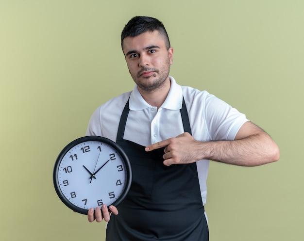 Fryzjer w fartuchu trzymający zegar ścienny wskazujący na niego palcem wskazującym, wyglądający pewnie