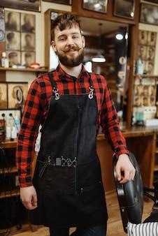 Fryzjer w fartuchu z narzędziami tnącymi. profesjonalny zakład fryzjerski to modne zajęcie. mężczyzna fryzjer w salonie fryzjerskim w stylu retro