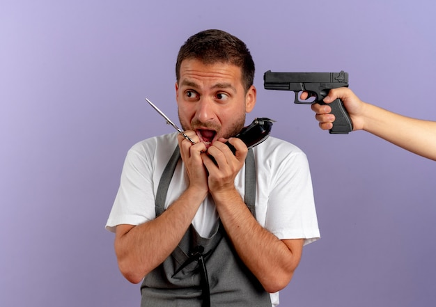 Fryzjer w fartuchu z nożyczkami i trymerem przestraszony, gdy ktoś celuje w niego z pistoletu