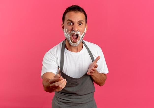 Fryzjer w fartuchu z pianką do golenia na twarzy trzymający brzytwę patrząc do przodu z wyciągniętymi rękami, pytając lub kłócąc się, stojąc nad różową ścianą