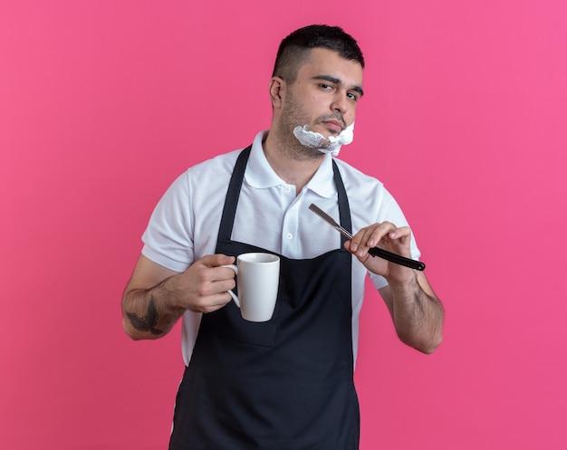 Fryzjer w fartuchu z pianką do golenia na twarzy zamierza się ogolić brzytwą patrząc na kamerę uśmiechając się pewnie trzymając kubek stojący na różowym tle