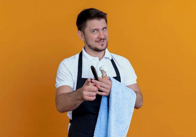 Fryzjer w fartuchu z ręcznikiem na dłoni trzymający pędzel do golenia z pianką i brzytwą patrząc na kamerę uśmiechnięty pewnie stojąc na pomarańczowym tle
