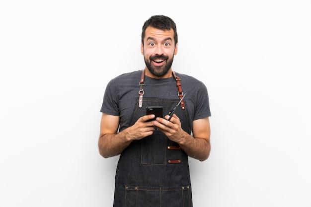 Fryzjer w fartuchu zaskoczony i wysyłający wiadomość