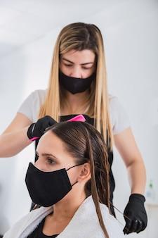 Fryzjer w gumowych rękawiczkach trzymający grzebień - fryzjer ze środkami bezpieczeństwa dla covid-19.