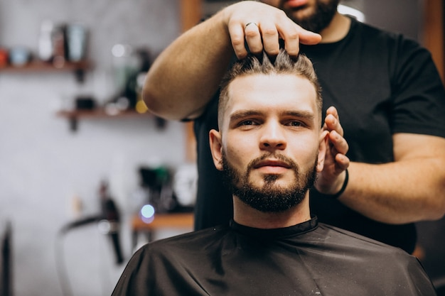 Fryzjer w sklepie fryzjerskim stylizuje włosy klienta