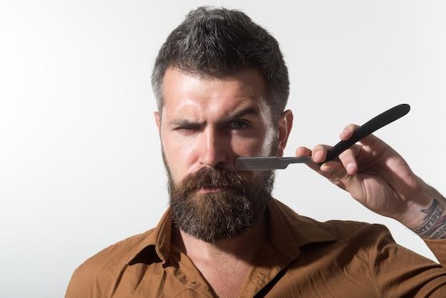 Fryzjer w stylowej koszuli demonstruje ostre ostrze swojej groźnej brzytwy atrakcyjnego fryzjera z