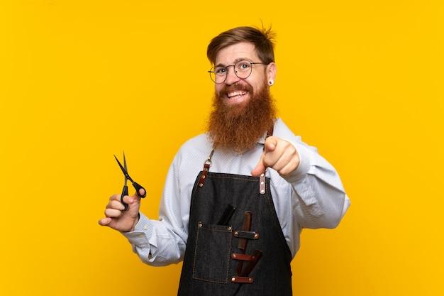 Fryzjer z długą brodą w fartuchu wskazuje na ciebie z pewnym siebie wyrazem twarzy
