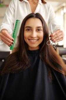 Fryzjer z grzebieniem i nożyczkami, kobieta w salonie fryzjerskim. stylistka i klientka w salonie fryzjerskim. biznes kosmetyczny, profesjonalna obsługa