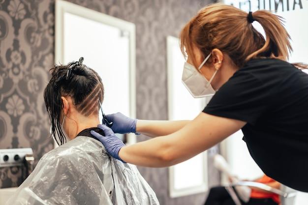 Fryzjer z maską do golenia klienta. ponowne otwarcie ze środkami bezpieczeństwa fryzjerów w pandemii covid-19