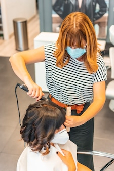 Fryzjer z maską i klientką, kończący falującą fryzurę do stu. ponowne otwarcie ze środkami bezpieczeństwa dla fryzjerów podczas pandemii covid-19. nowy normalny, koronawirus, dystans społeczny