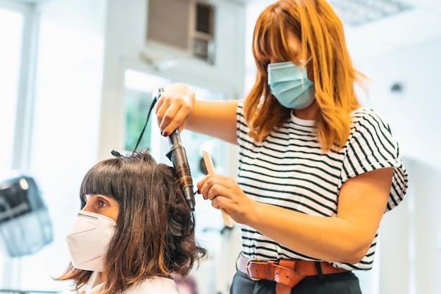 Fryzjer z maską i klientką, rozpoczynający falującą fryzurę. ponowne otwarcie ze środkami bezpieczeństwa dla fryzjerów podczas pandemii covid-19. nowy normalny, koronawirus, dystans społeczny