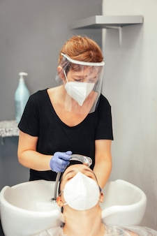 Fryzjer z maską i rękawiczkami myj włosy klienta wodą. ponowne otwarcie ze środkami bezpieczeństwa fryzjerów w pandemii covid-19