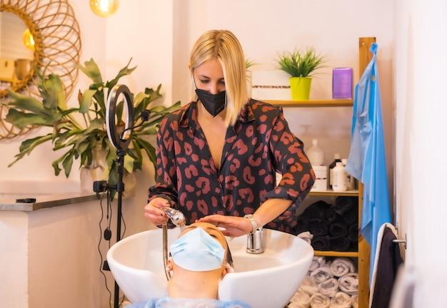 Fryzjer z maską ochronną myjącą włosy klientki mydłem i gorącą wodą. otwarcie ze środkami bezpieczeństwa dla fryzjerów w pandemii covid-19