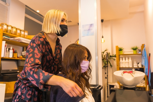 Fryzjer z maską ochronną na twarz, pokazującą klientowi efekt fryzury. środki bezpieczeństwa podczas pandemii covid-19