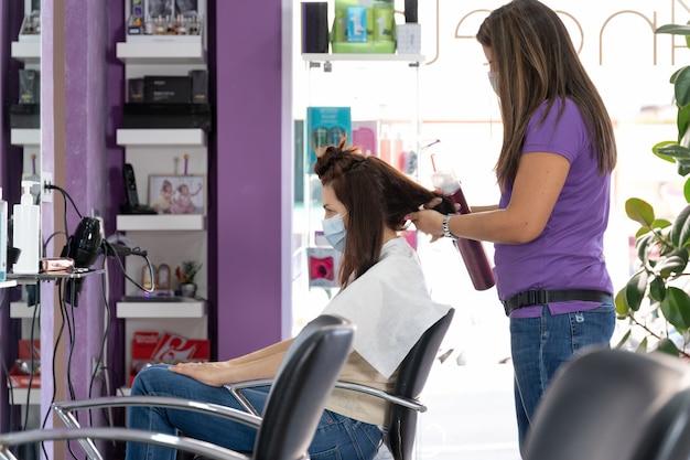 Fryzjer z maską przeczesuje klienta w swoim zakładzie