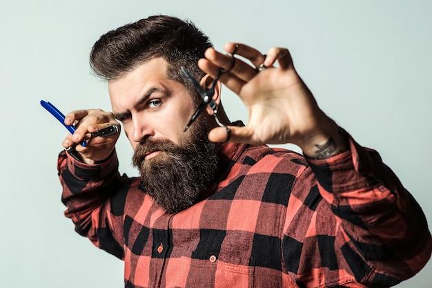 Fryzjer z nożyczkami i brzytwą. fryzjer sklep małej firmy. brodaty facet ze stylową fryzjerką na niebieskim tle