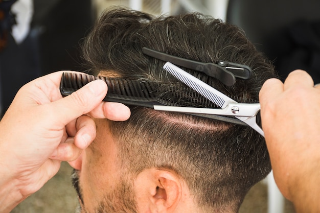 Fryzjer za pomocą nożyczek i grzebienia do cięcia włosów mężczyzny