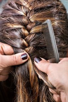 Fryzjer zaplatający włosy klienta